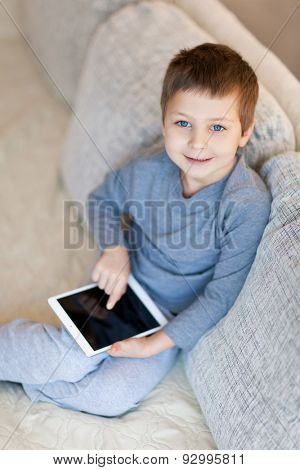 Little boy with iPad sitting on the sofa