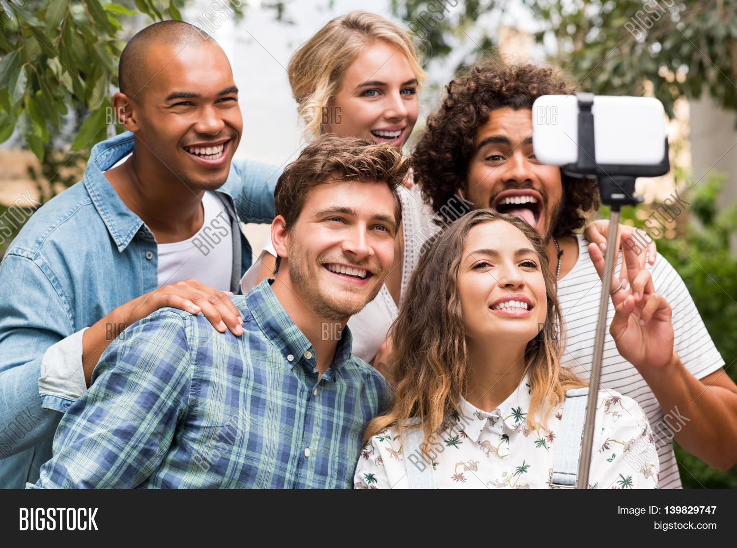 1fe8800e0de25 Happy friends with funny face taking a photo with a selfie stick. Group of  smiling