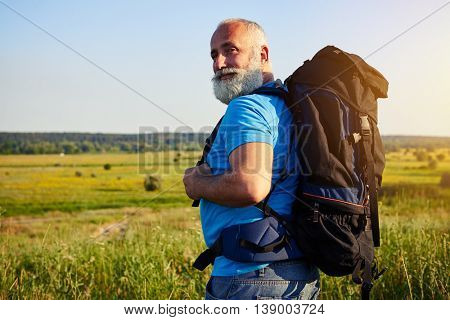 Close-up of physically fit aged man with rucksack who turned his head to smile at the camera while walking in the field on sunny summer day