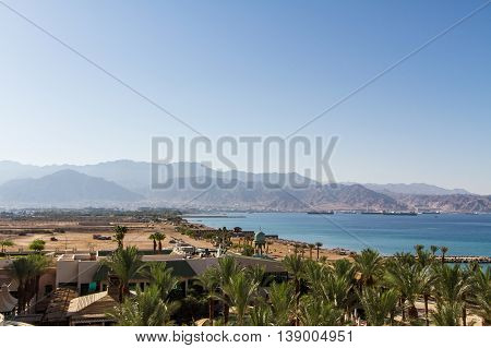 Panoramic view on Aqaba from central beach of Eilat - famous resort and recreational city in Israel .