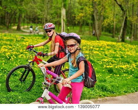 Bikes bicyclist girl. Girls wearing bicycle helmet and glasses with rucksack rides bicycle. Bicyclist children is looking at camera. Children ride on green grass and flowers in park.