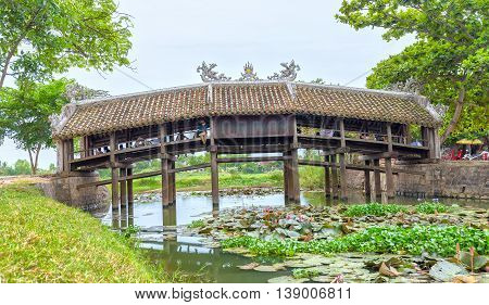 Thua Thien Hue, Vietnam - June 21st, 2015: Architecture bridge with wooden tile roofing structures on like a house on river to attract tourists to relax, below lilies blooming creating beauty idyllic countryside in Thua Thien Hue, Vietnam