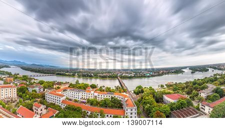 Hue, Vietnam - June 21st, 2015: Panorama city in afternoon with billowing clouds when storm comes, below  ancient red tile house as urban areas along river beautiful and idyllic in Hue, Vietnam