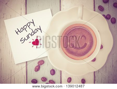 Happy Sunday on paper note with coffee cup on table