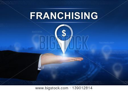 franchising button with business hand on blurred background