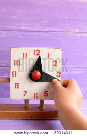 Kid learns to tell time on old wooden clock toy. Child pulls a hand to translate the time. How to teach child to read clock. Old wooden educational toy