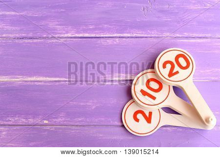 Educational toy for teaching kids numbers. Numbers two, ten, twenty. Early child development. How teach to recognize children the numbers. Purple wooden background with blank place for text