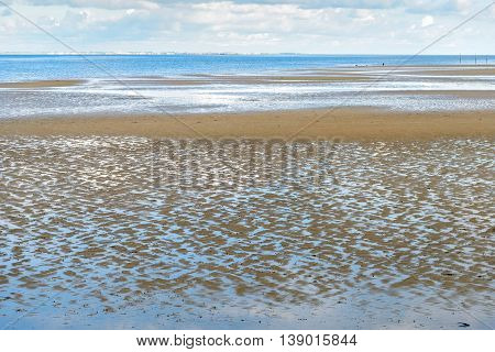 Dutch estuary at low tide on an early morning in the summer season. Little waves in the sand can be seen. The water reflects the cloudy sky.