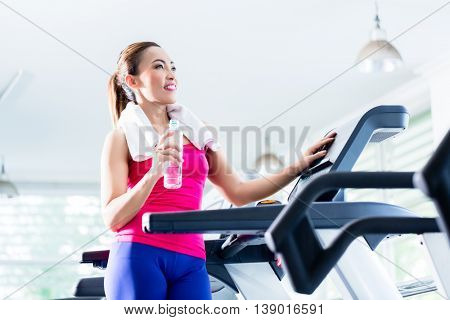 Smiling young woman on treadmill presenting water bottle as a reminder of sufficient hydration during workout