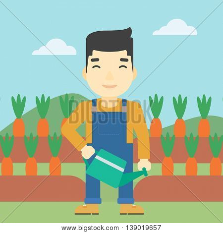 An asian farmer holding a watering can. Farmer watering carrots. Farmer standing on the background of carrots growing on field. Square layout.