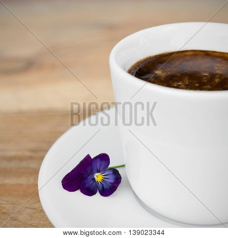 Cup of espresso coffee with flower arranged on old rustic wooden table