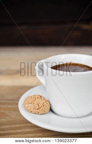 Cup of espresso with biscotti arranged on old rustic wooden table