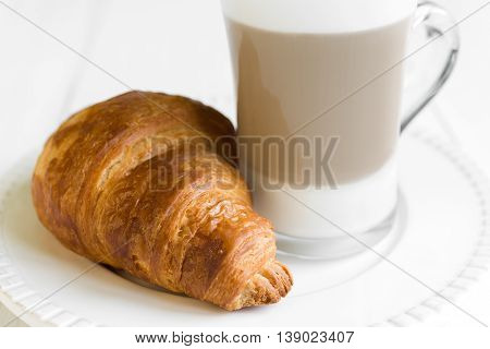 Croissant and glass of latte coffee on white plate and table