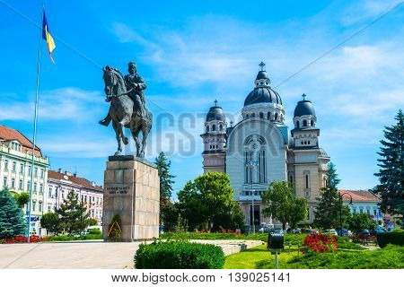 Traditional statue and building architecture in the main square of Targul Mures city, in Romania