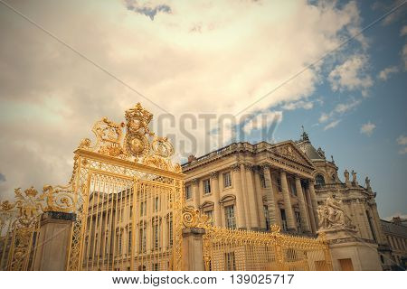 Versailles chateau. France. View of golden gate to palace. Royal residence near Paris. King's quarters. Famous touristic renaissance architecture landmark in summer.