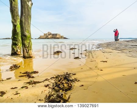 SAINT MALO, FRANCE - MAY 4 2014: The tourist takes photo of Fort National during low tide. Seashore Saint-Malo, Brittany, France