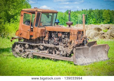 Old,abandoned ,rusty bulldozer on the field .