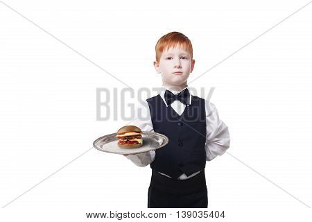 Little waiter stands with tray serving hamburger. Redhead child boy in suit plays restaurant servant, gives burger isolated at white background