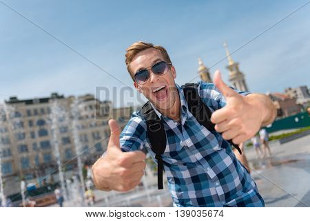 Add some craziness. Cheerful smiling handsome man thumbing up and standing near fountain while having a walk