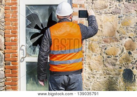 Building inspector with tablet PC near broken window