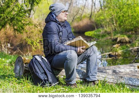 Man reading book in meadow near river