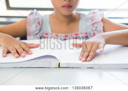 Midsection of blind girl reading braille book in classroom