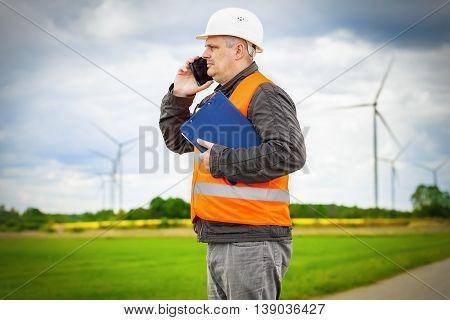 Electrician engineer talking on smart phone near Windmills