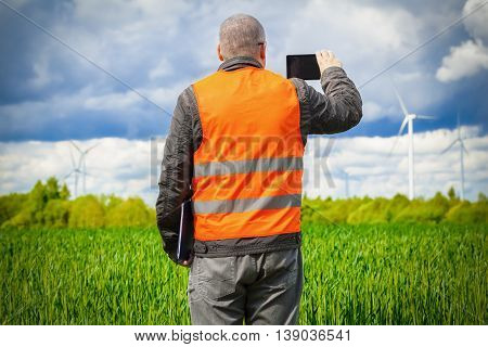 Farmer take pictures on smart phone near the green cereal field