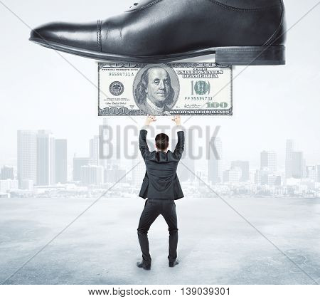 Business opression concept. Businessman with dollar banknote under giant shoe on abstract city background