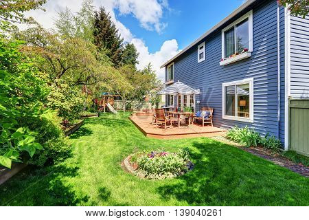 Wooden Walkout Deck In The Backyard Garden Of Blue Siding House.