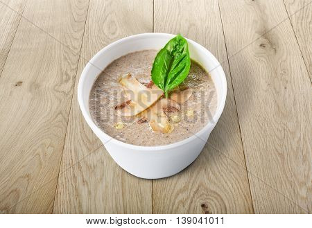 French cuisine hot food delivery - mushroom soup closeup in white plastic plate at natural wood background. Healthy eating concept