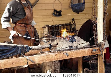 The annual festival in Kolomenskoye. Reconstruction of Ancient Rus. Blacksmith blows the bellows