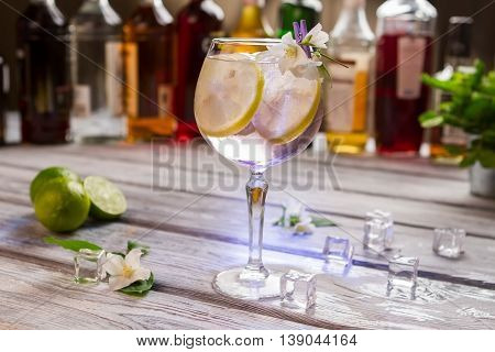 Cocktail with lemon in glass. White flowers and ice cubes. Tom collins served at nightclub. Alcoholic beverage with best gin.