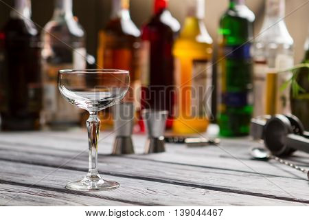 Empty coupe glass. Glass on gray wooden surface. Relax at the local bar. Many kinds of alcohol.