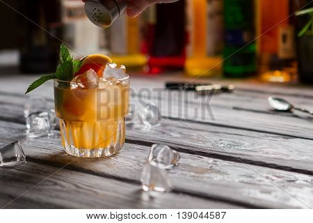Orange cocktail in a glass. Small jar with spice. Citrus fruit and cinnamon powder. Fresh cobas cocktail.