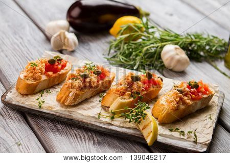 Grilled toasts with fish meat. Lemon slice and small capers. Bruschetta with chopped salmon. Traditional italian appetizer.