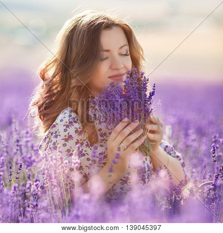 Young beautiful brunette woman with curly hair,long eyelashes and makeup,posing against the background of blooming purple lavender field mountain,dressed in a light summer dress,holding a bouquet of lavender and enjoys her scent closing his eyes