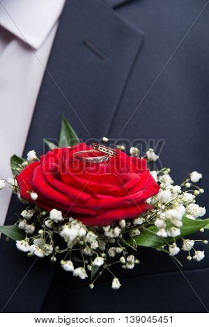 Wedding Rings Lie On The Flower Of A Red Rose