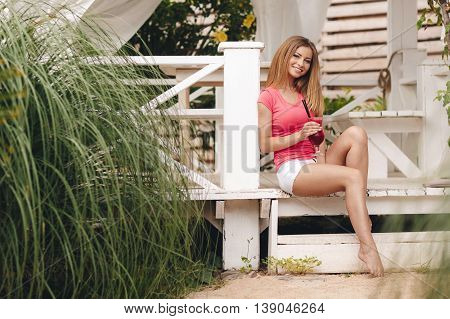 Summer portrait of a beautiful woman,brunette with long straight hair and gray eyes,a nice smile and beautiful white teeth,dressed in a red t-shirt and white shorts,resting in a country house sitting on a wooden porch with a fruity cocktail outdoors
