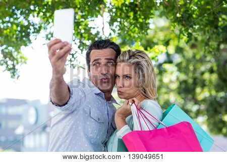 Couple puckering while taking selfie against trees in city