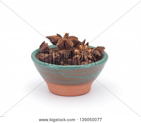 Star Anise In A Clay Sauce-boat Isolated On White Background