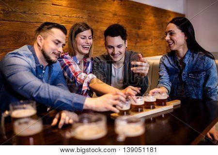 Happy friends enjoying beer at restaurant