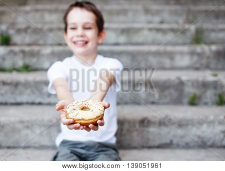 boy giving a donut. smiling child giving a donut to someone. the concept of generosity. selective focus. empty space for your text