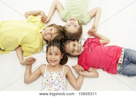 Circle of four young friends smiling and holding hands