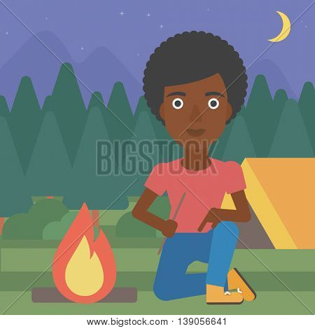 An african-american woman kindling campfire on the background of camping site with tent. Tourist relaxing near campfire. Woman sitting near campfire. Vector flat design illustration. Square layout.