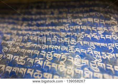 Mani stones in Nepalese village, ancient buddhist carved stones with sacred religious mantras written in Tibetan language