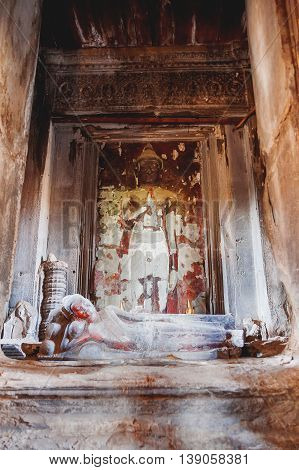 Room with scented candles Buddha sculpture and sacral decorations in Angkor Wat temple complex in Cambodia and the largest religious monument in the world. UNESCO World Heritage Site.