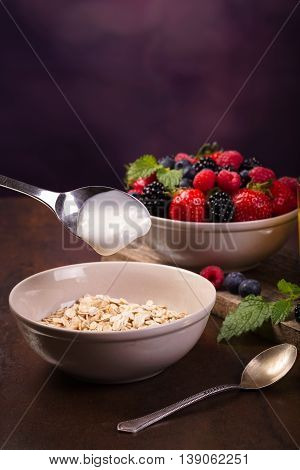 Spoon of yoghurt. Flavoring oatmeal with white yoghurt and some berries. Cup of fresh orange juice.