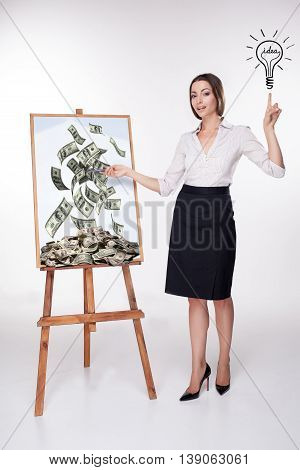 The young business woman presenting a lucrative and money idea on the board on white background.