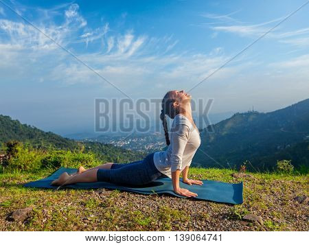 Yoga outdoors  - woman practices Ashtanga Vinyasa yoga Surya Namaskar Sun Salutation asana Urdhva Mukha Svanasana - upward facing dog pose in mountains in the morning